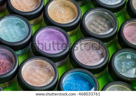 assortment make-up cosmetics powder in small closed pots in green box