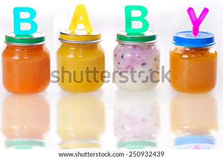 assortment of baby food in jars with letters making word baby on the top isolated on white - stock photo