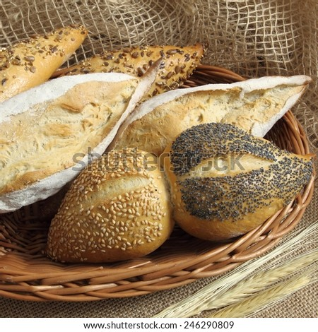 Assortment of baked bread  in basket on table. - stock photo