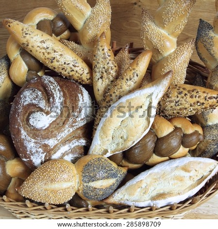 Assortment of baked bread  in basket on table - stock photo
