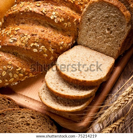 assortment of baked bread on wood table - stock photo