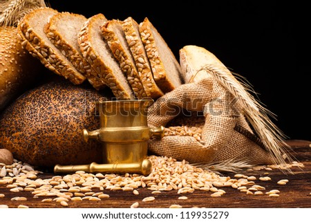 assortment of baked bread on wooden table and black background