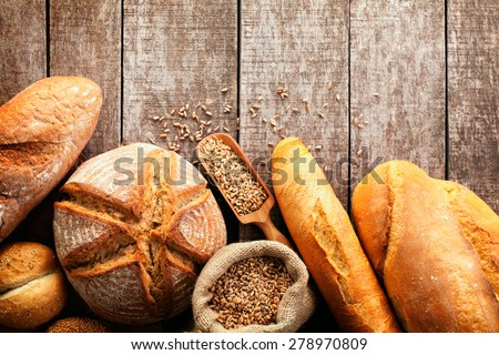 Assortment of baked bread on wooden table background - stock photo