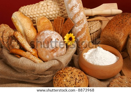 Assortment of baked breads on red background - stock photo