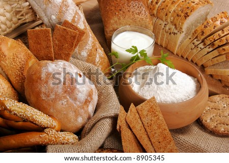 Assortment of baked breads with a bowl of flour - stock photo