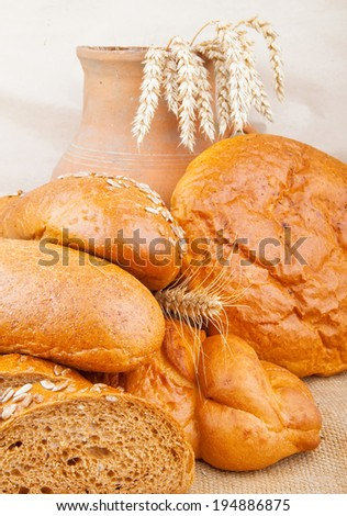 Assortment of baked breads with spikelets of wheat and pitcher on burlap fabric