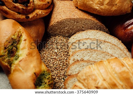 Assortment of baked delicious bread on wood table