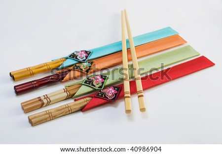 assortment of beautiful wooden chopsticks in colorful sleeves, isolated on light background - stock photo