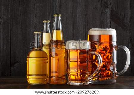 Assortment of beer glasses and bottles on table, dark wooden background - stock photo