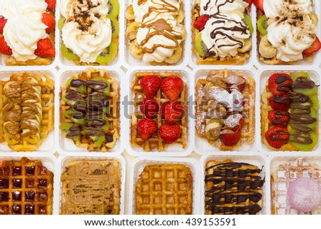 Assortment of Belgium waffles with different toppings: strawberries and kiwi fruits, chocolate or caramel sauces and cream. - stock photo