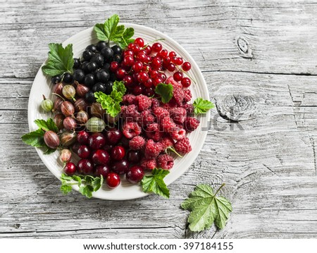 Assortment of berries - raspberries, gooseberries, red currants, cherries, black currants on a white plate on a wooden background. Healthy food, delicious summer dessert - stock photo