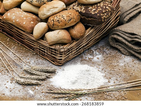 Assortment of breads in basket on wooden table - stock photo