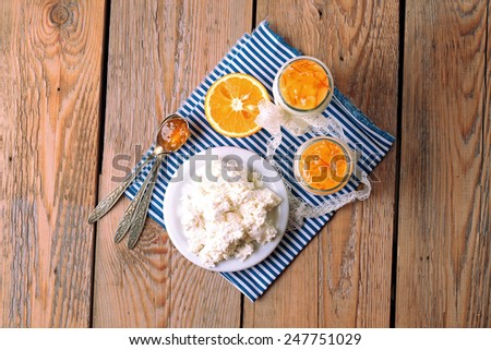 Assortment of breakfast products (homemade yogurt, cottage cheese; orange jam) on a wooden table. Top view, selective focus - stock photo