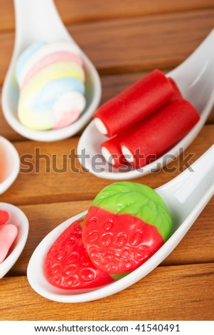 Assortment of candies in the spoons with soft shadow in the wooden background. Shallow depth of field - stock photo