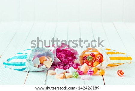 Assortment of candies in three striped decorated bags scattered over a white wooden table - stock photo