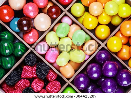 assortment of candy and gum in a wooden box   - stock photo