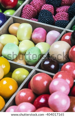 assortment of candy and gum in a wooden box. focus in the center of the frame - stock photo