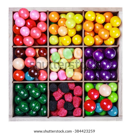 assortment of candy and gum in a wooden box on a white background - stock photo