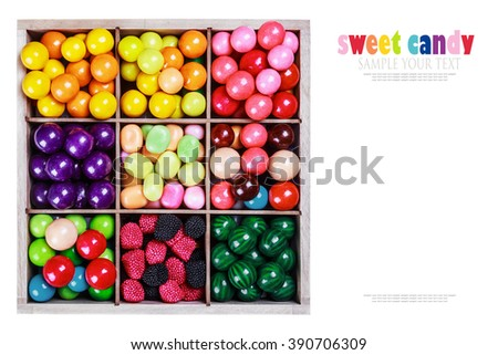 assortment of candy and gum in a wooden box on a white background. the text of your example and delete - stock photo