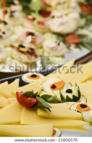 assortment of cheese and veg on a platter. - stock photo