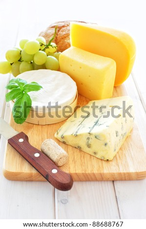 Assortment of cheese on a wooden platter - stock photo