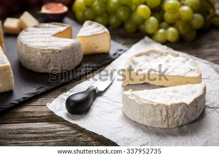 Assortment of cheese with fruits and grapes - stock photo