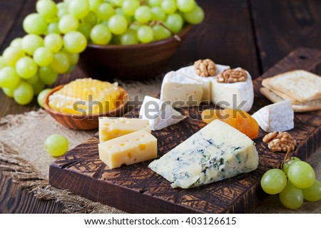 Assortment of cheese with honey, nuts and grape on a rustic cutting board wooden background