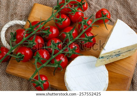 Assortment of cheese with red tomatoes on wooden board on burlap