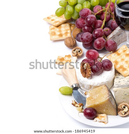 assortment of cheeses, glass of red wine, grapes and crackers, isolated on white - stock photo