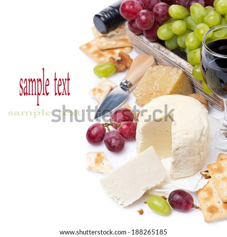 assortment of cheeses, red and green grapes, crackers and wine, isolated on white - stock photo