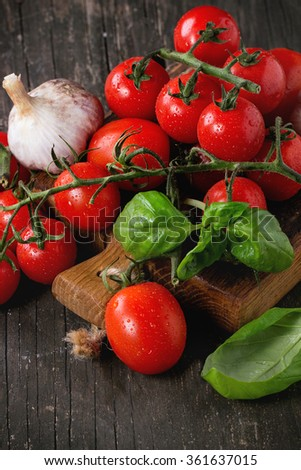 Assortment of colorful cherry tomatoes with garlic and basi on small cutting board over old wooden table.
