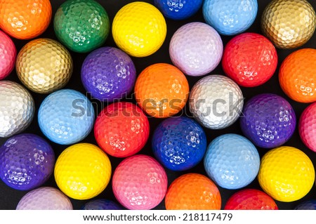 Assortment of colorful mini golf balls on black - stock photo