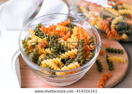 Assortment of colorful pasta in color bowls on wooden background - stock photo