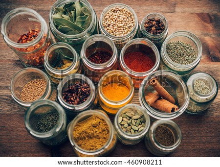 Assortment of colorful spices in glass jars.