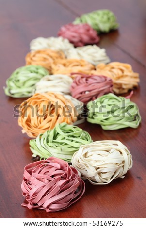 Assortment of colorful tagliatelle pasta dyed with natural dye from carrots, potatoes, spinach and beetroot - stock photo