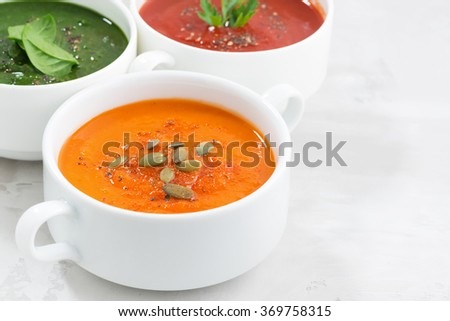 assortment of colorful vegetable cream soup on and white background, closeup