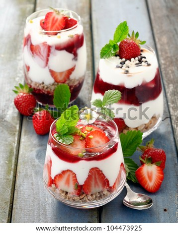 Assortment of creamy gourmet strawberry desserts layered in decorative patterns in individual glass containers - stock photo
