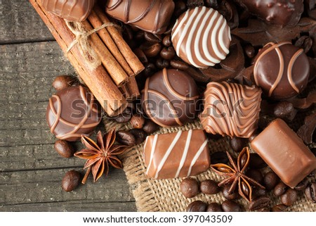 Assortment of dark, white and milk chocolate stack, chips. Chocolate and coffee beans on rustic wooden sacking background. Spices, cinnamon. Selective macro focus. Chocolates background. Sweets - stock photo