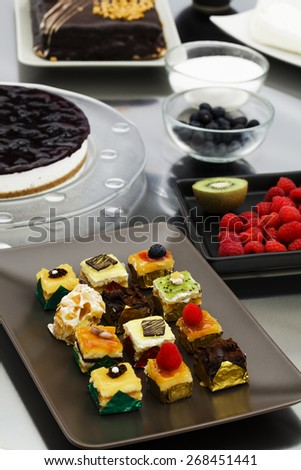 Assortment of delicious cakes and petit four pastries - stock photo
