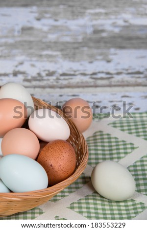 Assortment of different color, fresh, chicken eggs in a basket. Green shade kitchen textile background.