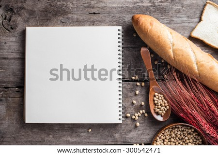Assortment of different types of bread and note book on wood background - stock photo