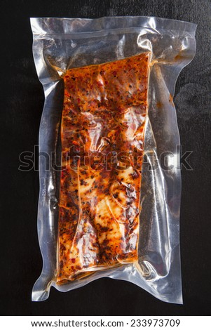 Assortment of different types of fresh spicy Italian sausages packaged in plastic vacuum a black background - stock photo