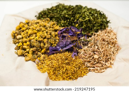 Assortment of dried herb and tea on white  - stock photo