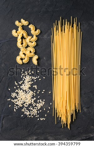 Assortment of dry pasta spaghetti, orzo, noodles and creste di gallo over black textured background. Top view - stock photo