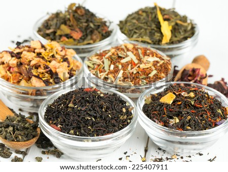 assortment of dry tea in glass bowls on wooden surface - stock photo