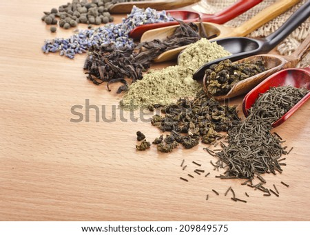 assortment of dry tea in scoops close up on wooden background - stock photo