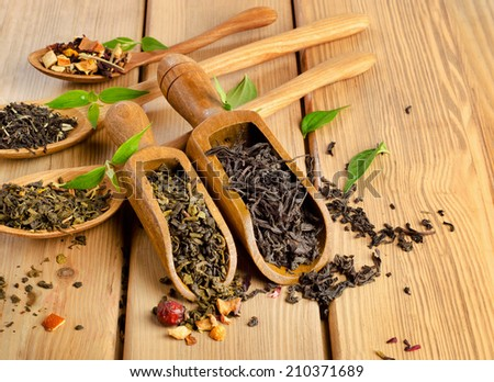 Assortment of dry tea in spoon on a  wooden background. Selective focus - stock photo