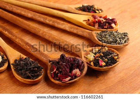 assortment of dry tea in spoons, on wooden background - stock photo