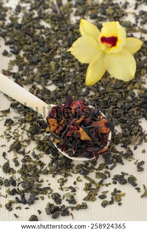 assortment of dry tea in spoons with flower, on wooden background