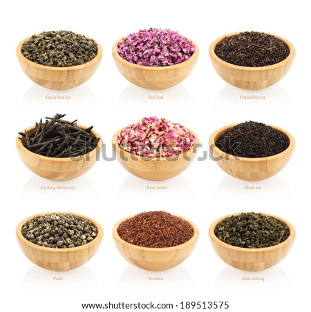 Assortment of dry tea in wooden bowls. Isolated on white background - stock photo
